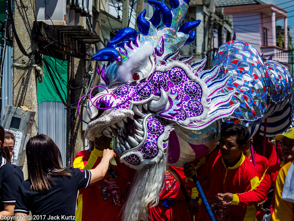 "02 JUNE 2017 - SAMUT SAKHON, THAILAND: Dragon dancers perform during the parade for the City Pillar Shrine in Samut Sakhon. The Chaopho Lak Mueang Procession (City Pillar Shrine Procession) is a religious festival that takes place in June in front of city hall in Samut Sakhon. The ""Chaopho Lak Mueang"" is  placed on a fishing boat and taken across the Tha Chin River from Talat Maha Chai to Tha Chalom in the area of Wat Suwannaram and then paraded through the community before returning to the temple in Samut Sakhon. Samut Sakhon is always known by its historic name of Mahachai.      PHOTO BY JACK KURTZ"
