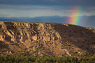 A segment of a rainbow formed over Otowi Mesa, with the Sangre de Cristo Mountains in the distance. The area of ash-fall tuff on the east side of the Jemez Mountains formed a plateau know as the Pajarito Plateau, which eroded into canyons and mesas composed of the distinctive soft rock. The caves at the base of the cliff are abandonded Indian caves that were carved by hand. © 2011 David A. Ponton