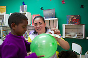 C&A volunteer, Daniele, decorating a balloon with children at their community library, Biblioteca Chocolatao, Porte Alegre, Brazil.