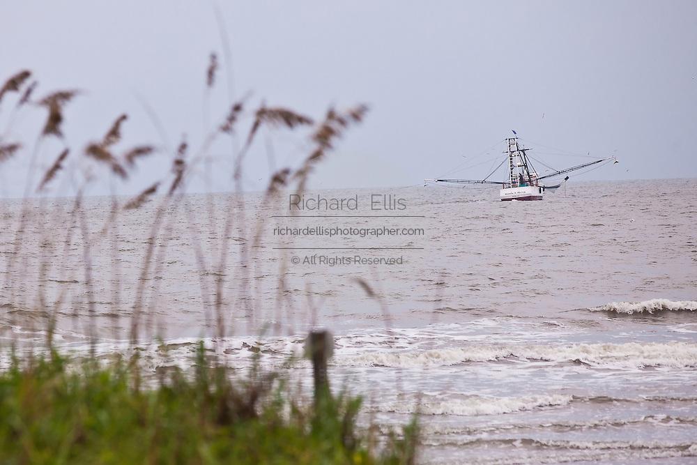 A shrimp boat trawls off the beach of Sullivan's Island, SC.