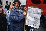 """Student shows an elargement of a cartoon by Vauro, published on the leftist daily newspaper il Manifesto, at a rally called by Unions against the new law to depenalize the unlawful financing of political parties in Milan, March 13, 1993. The cartoon shows a man that tells to another """"But you are covered by shit!"""" and the other one answer """"don't overstate, pass the sponge is enough"""". The law - called pass the sponge - was introduced by Giovanni Conso, Minister of Justice of Giuliano Amato cabinet. ..Studente con un cartello che riproduce una vignetta di Vauro comparsa sul quotidiano il Manifesto alla manifestazione convocata dai sindacati contro il decreto legge di depenalizzazione del finanziamento illecito dei partiti - detta colpo di spugna -, a Milano, 13 marzo 1993. Il decreto legge é stata proposto dal ministro della giustizia Giovanni Conso del governo Amato."""