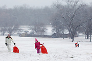 Lauren Parnell, 9, left, and Ella Sweeney, 6, climb to the top of the hill for another sled run at Flag Pole Hill Park in Dallas, Texas, on December 25, 2012.  (Stan Olszewski/The Dallas Morning News)