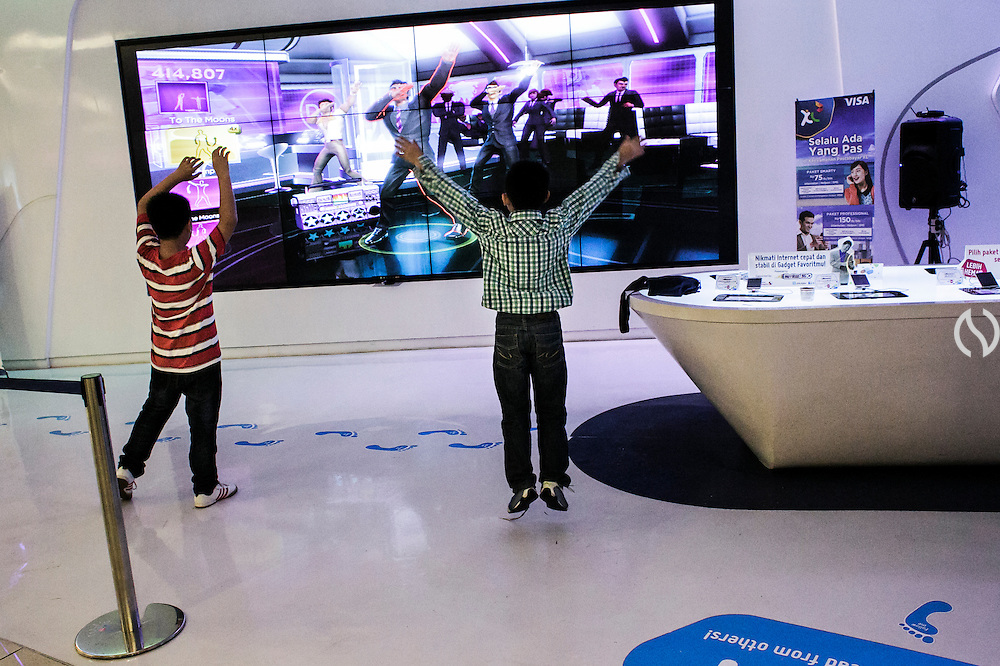 JAKARTA - INDONESIA; SATURDAY, SEPTEMBER 13, 2014; INDONESIA ECONOMIC RISING: Kids play an interactive game at communication provider store at Central Park Mall, Jakarta, Indonesia, Saturday, September 13, 2014. According to Asian Development Bank's 2014 report, Indonesia economy growth potential is in creative industry after for years relies heavily on natural resources such as mineral mining and palm oil. By the presidency of Joko Widodo, as a product of the third people election after the People Power Revolution in 1998, Indonesia is more confident in the economy growth and optimistic to become equal in quality to Brazil and China's economy growth. The emerging of Indonesia economy for the last one and a half decade after the end of Suharto's Dictatorship has been in significant way, the per capita growth has reached 400% under Susilo Bambang Yudhoyono presidency. Indonesia is home for 74 million of middle class as estimated by Boston Consulting Group, and  will double in 2020.
