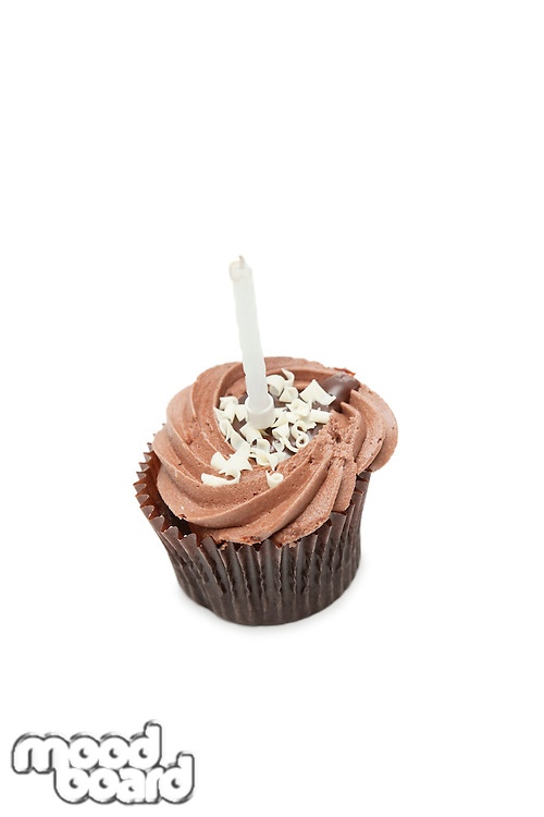 Chocolate cupcake with candle over white background