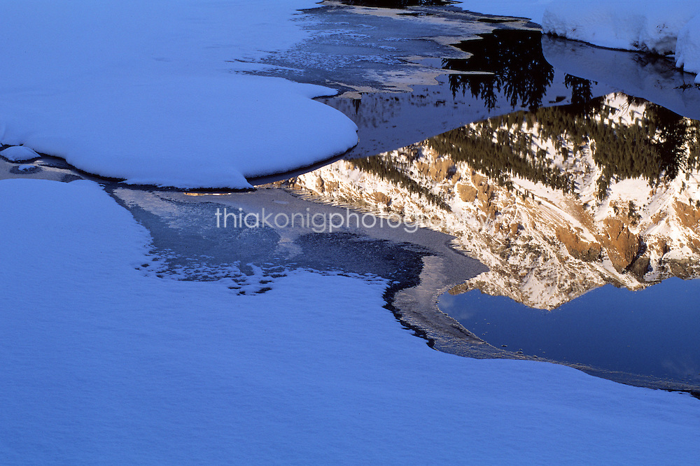 Reflection of snow covered mountain in beaver pond, winter, Sun Valley, Idaho.