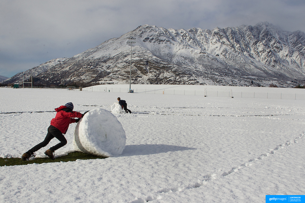 Simon Healy, 11 (front) and his brother Nicholas, 7, from Auckland,  use all their effort to make large snowballs at the Events Centre Fields, Queenstown, with the Remarkables mountain range in the background after fresh winter snow falls. Queenstown, Central Otago, South Island, New Zealand. 10th July 2011. Photo Tim Clayton.