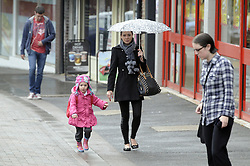 © Licensed to London News Pictures. 12/09/2013<br /> Mother and child walking near the station down Pettswood high street.<br /> Wet weather in the South East this morning for Commuters at Pettswood train station,Greater London near Bromley.<br /> Photo credit :Grant Falvey/LNP