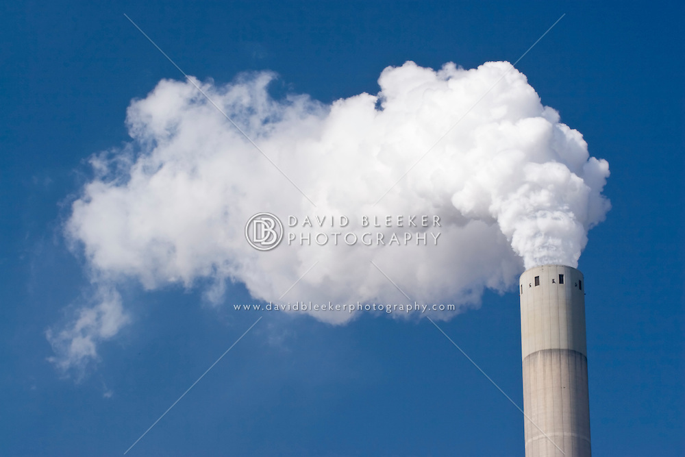 Smoke pooring from a chimney at the coal fired NUON Powerplant Amsterdam against a blue sky.