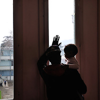 Man and child looking out, at a centre run by the Hospice Generale for refugees and asylum seekers.