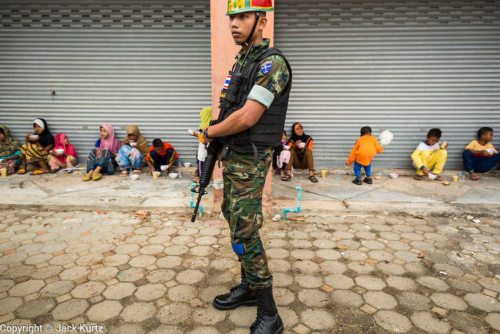 07 JULY 2013 - NARATHIWAT, NARATHIWAT, THAILAND:  An armed Royal Thai Marine provides security at a civil affairs project in Narathiwat. Royal Thai Marines in Narathiwat province held a special ceremony Sunday in advance of Ramadan. They presented widows, orphans and indigent people with extra rice and food as a part of the Thai government's outreach to resolve the Muslim insurgency that has wracked southern Thailand since 2004. The Holy Month of Ramadan starts on about July 9 this year. Muslims are expected to fast from dawn to dusk, engage in extra prayers, recitation of the Quran and perform extra acts of charity during Ramadan. It is the holiest month of the year for Muslims.   PHOTO BY JACK KURTZ