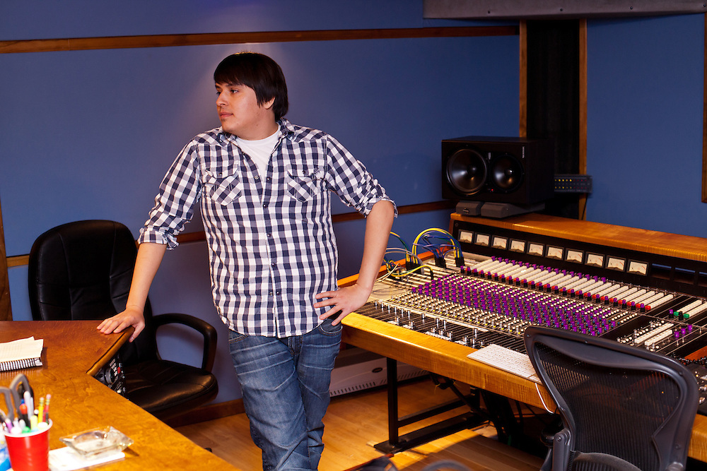 A man stands next to a soundboard and sound booth in a recording studio.