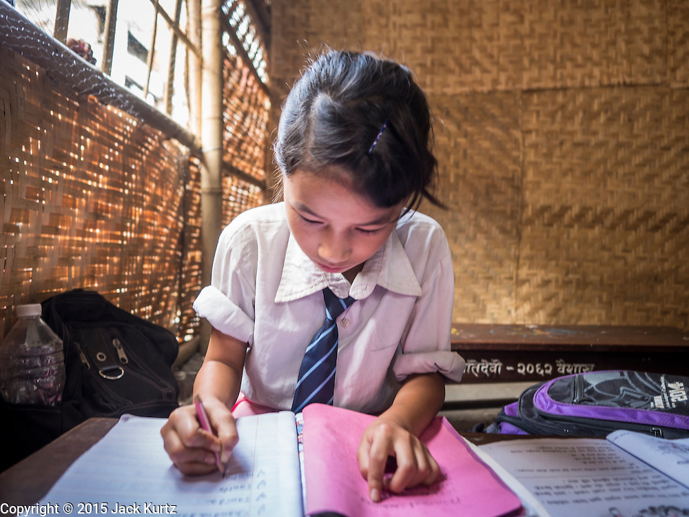 03 AUGUST 2015 - KATHMANDU, NEPAL:  A girl studies in a temporary school in central Kathmandu. Parts of her existing school were damaged in the earthquake and officials are afraid to use the existing structure, so they have set up a temporary school made of woven matting. The Nepal Earthquake on April 25, 2015, (also known as the Gorkha earthquake) killed more than 9,000 people and injured more than 23,000. It had a magnitude of 7.8. The epicenter was east of the district of Lamjung, and its hypocenter was at a depth of approximately 15km (9.3mi). It was the worst natural disaster to strike Nepal since the 1934 Nepal–Bihar earthquake. The earthquake triggered an avalanche on Mount Everest, killing at least 19. The earthquake also set off an avalanche in the Langtang valley, where 250 people were reported missing. Hundreds of thousands of people were made homeless with entire villages flattened across many districts of the country. Centuries-old buildings were destroyed at UNESCO World Heritage sites in the Kathmandu Valley, including some at the Kathmandu Durbar Square, the Patan Durbar Squar, the Bhaktapur Durbar Square, the Changu Narayan Temple and the Swayambhunath Stupa. Geophysicists and other experts had warned for decades that Nepal was vulnerable to a deadly earthquake, particularly because of its geology, urbanization, and architecture.    PHOTO BY JACK KURTZ
