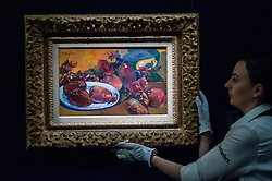 "© Licensed to London News Pictures. 19/06/2015. London, UK. A Sotheby's staff member shows Paul Gauguin's ""Nature morte aux mangos"" (est. £10m - £15m), at Sotheby's Impressionist, Modern & Contemporary Art preview, ahead of the sale on 24 June 2015. Leading the sale are Kazimir Malevich's, ""Suprematism, 18th Construction"" and Edouard Manet's ""Le Bar aux Folies-Bergère"".  Photo credit : Stephen Chung/LNP"