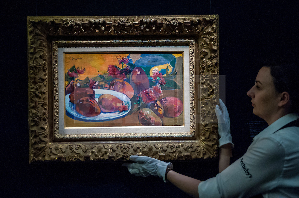 """© Licensed to London News Pictures. 19/06/2015. London, UK. A Sotheby's staff member shows Paul Gauguin's """"Nature morte aux mangos"""" (est. £10m - £15m), at Sotheby's Impressionist, Modern & Contemporary Art preview, ahead of the sale on 24 June 2015. Leading the sale are Kazimir Malevich's, """"Suprematism, 18th Construction"""" and Edouard Manet's """"Le Bar aux Folies-Bergère"""".  Photo credit : Stephen Chung/LNP"""