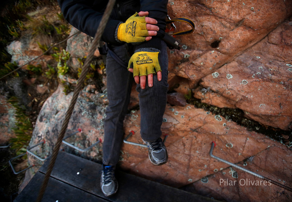 """A guest rests after climbing at the Skylodge Adventure Suites in the Sacred Valley in Cuzco, Peru, August 14, 2015. Tourists taking on an arduous climb up the steep cliff face of Peru's Sacred Valley are being rewarded for their efforts by being able to spend the night in transparent mountaintop sleeping pods at the """"Skylodge Adventure Suites"""". To reach the pods, visitors need to climb 400 metres of via ferrata (a steel cable and rungs) up the valley side or hike an intrepid trail through zip lines. REUTERS/Pilar Olivares"""