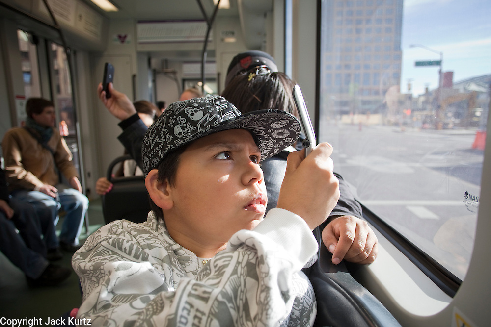 27 DECEMBER 2008 -- PHOENIX, AZ: At 10:04AM Angel Andazola (CQ) 11, from Phoenix peers out the window of the train as it cruises through downtown Phoenix.  Metro Light Rail started running Saturday, Dec. 28. The light rail line is 20 miles long and cost $1.4 billion dollars. PHOTO BY JACK KURTZ