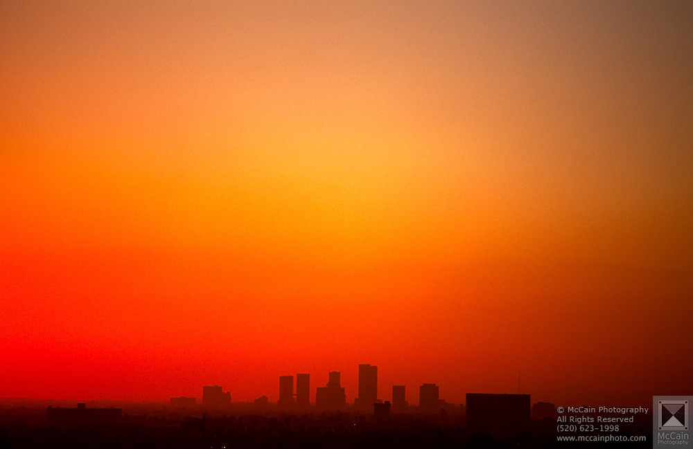View of downtown Phoenix skyline during a bright orange sunset, Phoenix, Arizona..Subject photograph(s) are copyright Edward McCain. All rights are reserved except those specifically granted by Edward McCain in writing prior to publication...McCain Photography.211 S 4th Avenue.Tucson, AZ 85701-2103.(520) 623-1998.mobile: (520) 990-0999.fax: (520) 623-1190.http://www.mccainphoto.com.edward@mccainphoto.com
