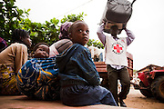 Women and children wait while a Benin Red Cross volunteer unloads blankets from a trailer during a UNICEF-sponsored distribution session for flood victims in Athieme, Benin  on Monday October 25, 2010. UNICEF donated water treatment tablets, mosquito nets and soap to affected families, while other partner organizations offered blankets, floormats, and buckets.