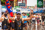 13 APRIL 2014 - BANGKOK, THAILAND: A tourist comes out of a water fight on Khao San Road, Bangkok's backpacker district, on the first day of Songkran. Songkran is celebrated in Thailand as the traditional New Year's Day from 13 to 16 April. Songkran is in the hottest time of the year in Thailand, at the end of the dry season and provides an excuse for people to cool off in friendly water fights that take place throughout the country. Songkran has been a national holiday since 1940, when Thailand moved the first day of the year to January 1.    PHOTO BY JACK KURTZ