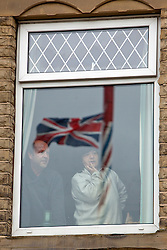© Licensed to London News Pictures. 09/04/2012. Gawthorpe , West Yorkshire / UK. The World Coal Carrying Championships . A man and a woman look from their window at the race with the finishing marker , the village maypole , refelcted in their window .. Each year men and women race the streets of Gawthorpe carrying huge sacks of Coal. The event starts from Owl Lane, outside the Royal Oak where both men and women race with a sack of coal,  approx one mile, 1108. 25 yards to be precise, to secure the best time. To qualify for completion of the race, the sack must be dropped on the Village Green where the traditional Maypole is situated in the heart of the Gawthorpe. further info on http://www.gawthorpemaypole.org.uk/?page_id=21. Photo credit : Chris Bull/LNP