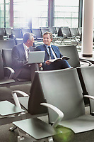 Portrait of business people sitting while waiting for boarding in airport