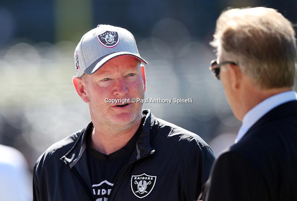 Oakland Raiders offensive coordinator Bill Musgrave talks to Denver Broncos general manager John Elway before the 2015 NFL week 5 regular season football game against the Denver Broncos on Sunday, Oct. 11, 2015 in Oakland, Calif. The Broncos won the game 16-10. (©Paul Anthony Spinelli)