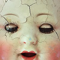 Close up of old fashioned porcelain dolls face with cracked paint