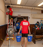 Up With People cast members Tomohiro Hayashi from Japan and Maxine Chen from Taiwan apply a fresh coat of paint to the walls while Diane Goldsmith from Texas and Adolfo Lara from Mexico head upstairs for cleaning during their community service at the Congregational Church Wednesday morning.  (Karen Bobotas/for the Laconia Daily Sun)