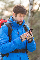 Young male hiker using smart phone in forest