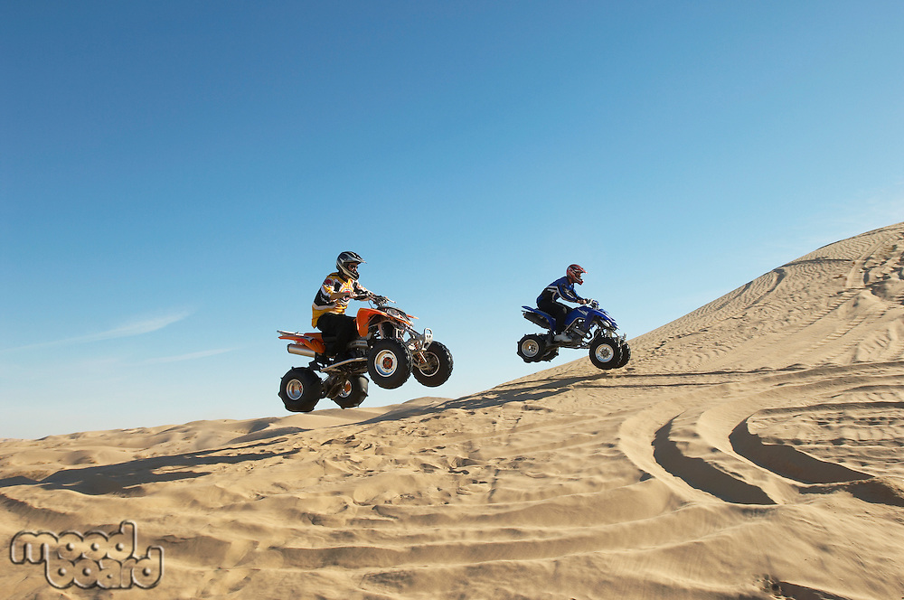Men doing wheelies on quad bikes in desert