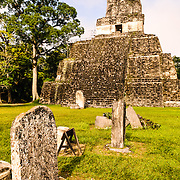 The Temple of the Masks, or Temple 2, in the Tikal Maya ruins in northern Guatemala, now enclosed in the Tikal National Park. In the foreground is a series of stela on the Main Plaza that once held commemorative inscriptions but that have since worn away over time. Visitors can climb wooden steps at the left of the pyramid to near the top. The section at the very top of the pyramid was once decorated in giant carved masks, only parts of which are still visible, and the entire pyramid would have been painted in bright colors.