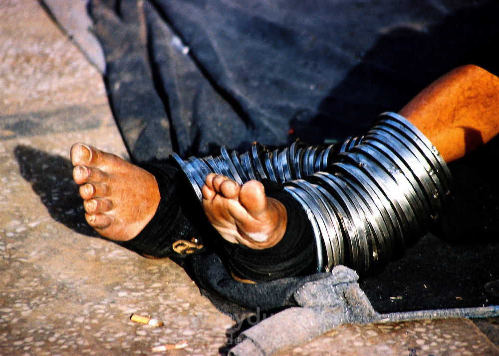 Pakistan, Sehwan Sharif, 2004. Adorned with some forty pounds of steel around his arms and legs, a devotee spiritually chains himself to the outer gates of the tomb of Hazrat Lal Qalander.