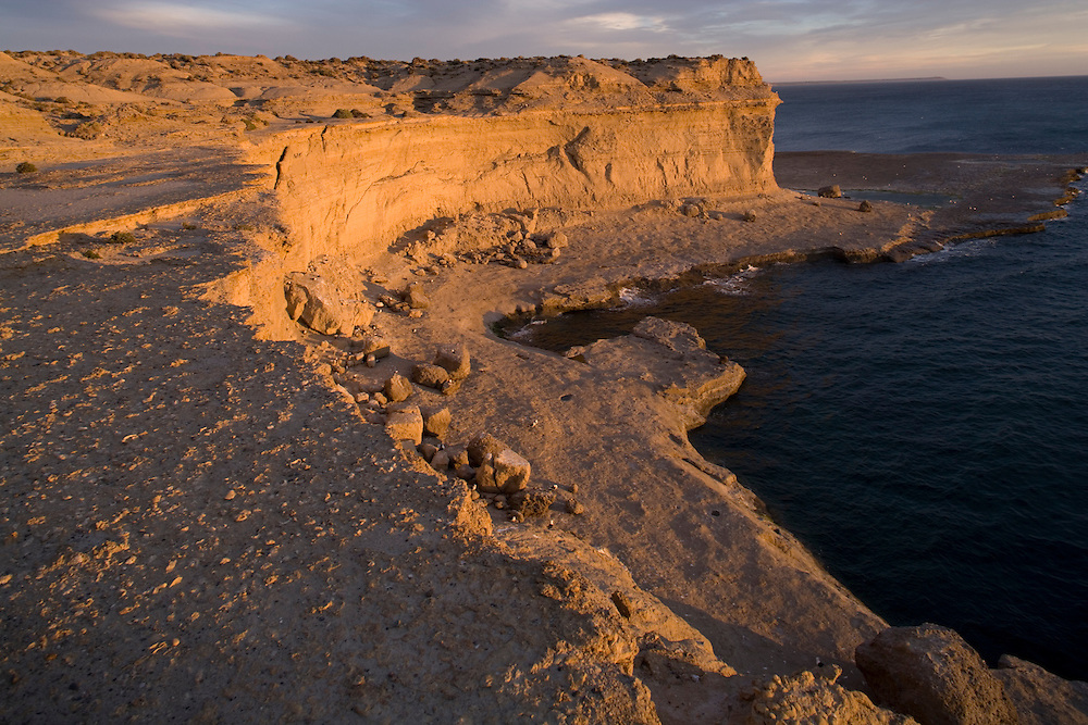 Argentina, Chubut Province, Puerto Piramedes, Setting sun lights cliffs of Peninsula Valdes along Atlantic Ocean coastline