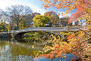 Bow Bridge spans the Lake, surrounded by fall colors in Central Park, New York City in Autumn season.