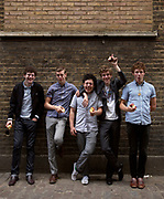 Young men leaning against a wall laughing and eating apples.