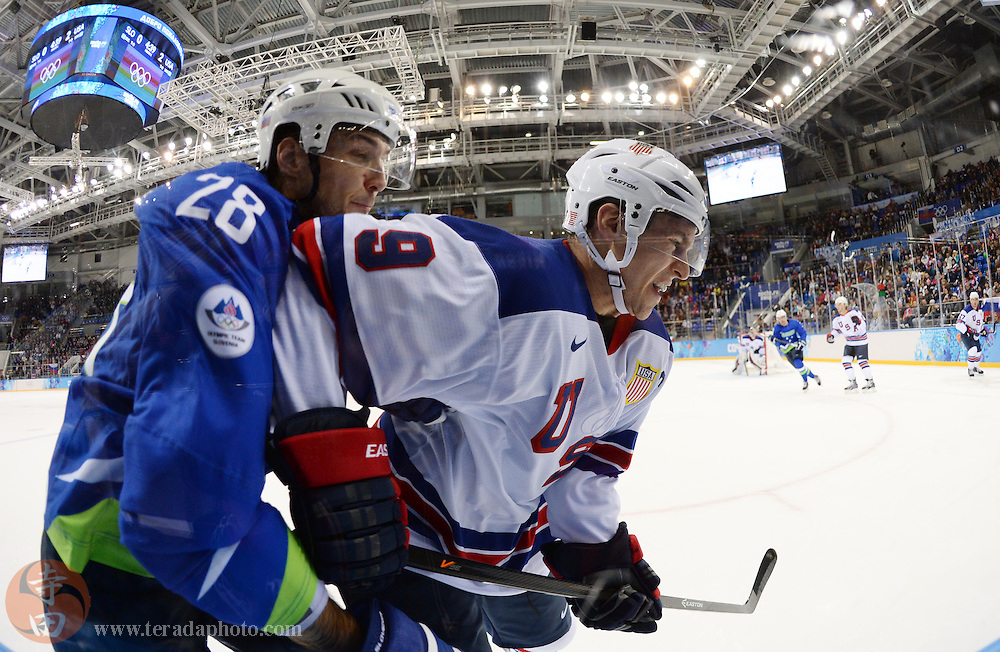 Feb 16, 2014; Sochi, RUSSIA; USA forward Zach Parise (9) chases after the puck with Slovenia defenseman Ales Kranjc (28) along the boards in a men's ice hockey preliminary round game during the Sochi 2014 Olympic Winter Games at Shayba Arena.