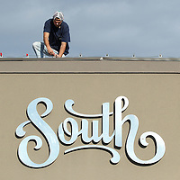 Adam Robison | BUY AT PHOTOS.DJOURNAL.COM<br /> Justin Hughes, an employee at South, changes out the light bulbs on the roofline of the building from clear to pink bulbs for breast cancer awareness month Thursday afternoon in Tupelo.