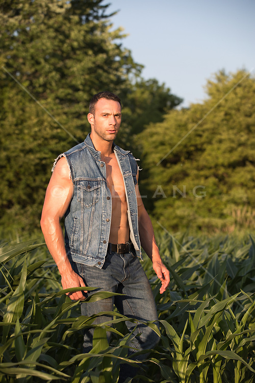hot guy in a trucker denim jacket standing in a field