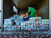 """04 DECEMBER 2018 - BANGKOK, THAILAND:  A man delivering single use plastic bags to shops in Khlong Toei market does paperwork in the back of his truck. The issue of plastic waste became a public one in early June when a whale in Thai waters died after ingesting 18 pounds of plastic. In a recent report, Ocean Conservancy claimed that Thailand, China, Indonesia, the Philippines, and Vietnam were responsible for as much as 60 percent of the plastic waste in the world's oceans. Khlong Toey (also called Khlong Toei) Market is one of the largest """"wet markets"""" in Thailand. December 4 was supposed to be a plastic free day in Bangkok but many market venders continued to use plastic.    PHOTO BY JACK KURTZ"""