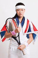 Confident female tennis player with British flag against white background
