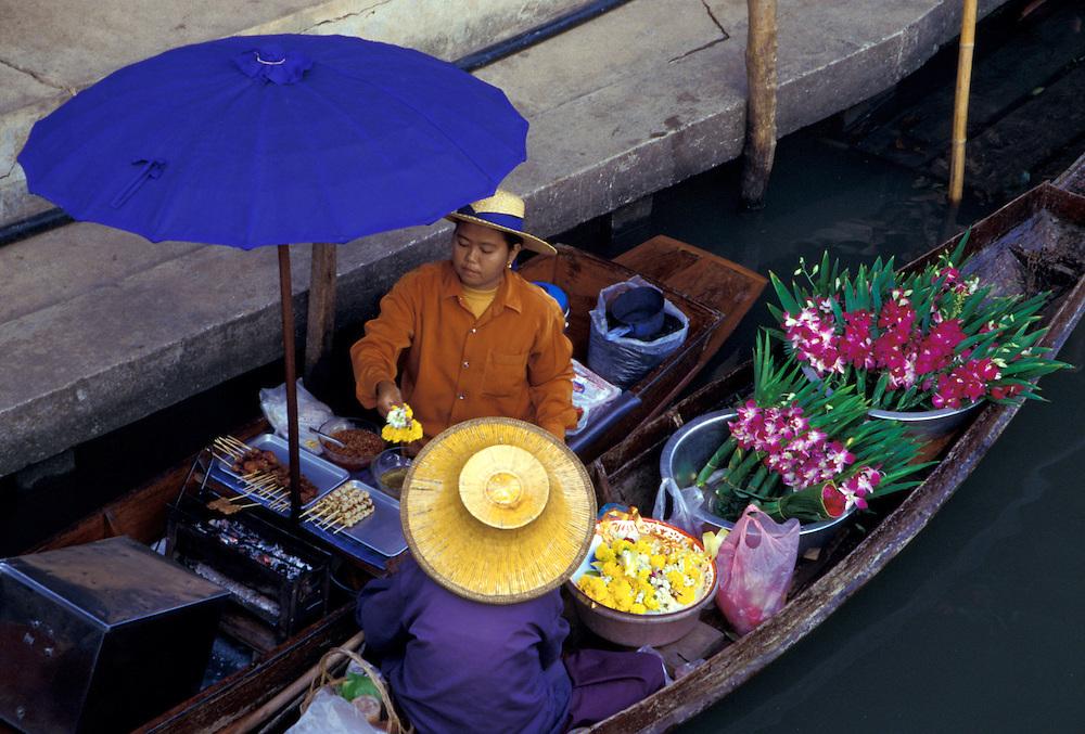Asia, Thailand, 104 km southwest of Bangkok. Damnoen Saduak Floating Market. Woman buys flowers while cooking on canoe under large umbrella