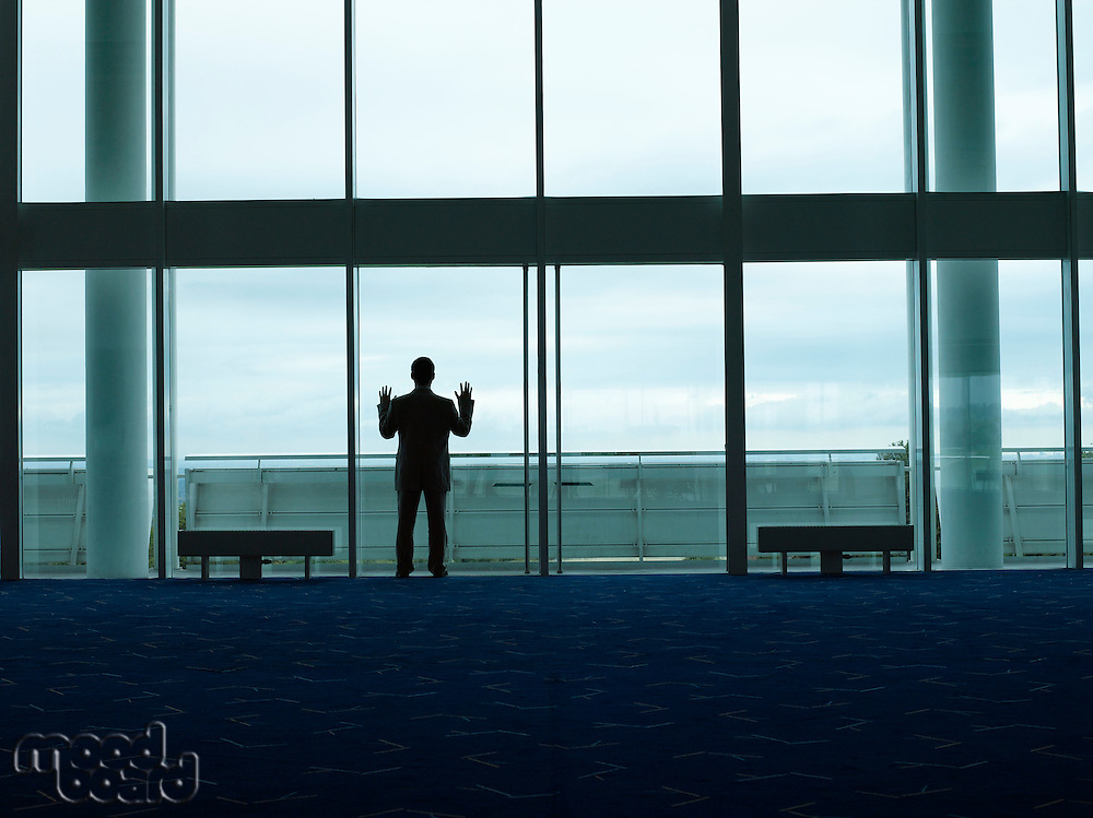 Businessman standing Looking out Window back view