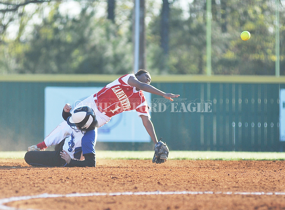 Lafayette High's Jada McIntosh (1) is upended after forcing out Senatobia's Emily Patrick (23) in girls softball action in Oxford, Miss. on Tuesday, April 15, 2014.