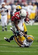 Arizona Cardinals running back Beanie Wells (26) runs over Green Bay Packers cornerback Tramon Williams (38) for a first down near the Packers 11 yard line during the NFC Wild Card Game against the Green Bay Packers, January 10, 2010 in Glendale, Arizona. The Cardinals won the game 51-45 in overtime. ©Paul Anthony Spinelli