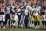 NFL umpire Mark Pellis (131), field judge Buddy Horton (82), and back judge Perry Paganelli (46) try to break up a melee after a second quarter penalty is called on the Cincinnati Bengals for unnecessary roughness during the Pittsburgh Steelers NFL AFC Wild Card playoff football game against the Cincinnati Bengals on Saturday, Jan. 9, 2016 in Cincinnati. The Steelers won the game 18-16. (©Paul Anthony Spinelli)