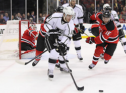 Oct 13; Newark, NJ, USA; Los Angeles Kings center Mike Richards (10) passes the puck after a save by New Jersey Devils goalie Martin Brodeur (30) during the first period at the Prudential Center.