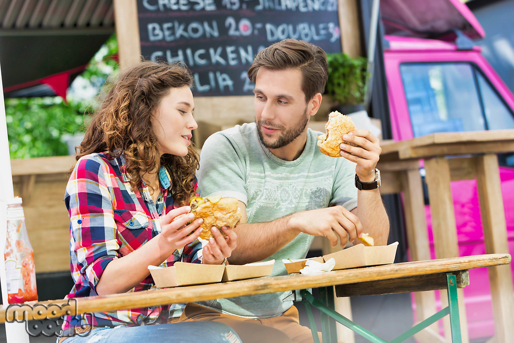 Young attractive couple eating hamburgers against food truck