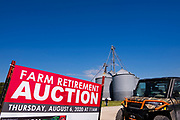 "06 AUGUST 2020 - FAIRFIELD, IOWA: A sign announcing the retirement auction on the Adam Farm near Fairfield. Gary Adam, 72 years old, has been farming in the Fairfield area since 1971. He decided to retire this year because he wants to travel and because it's so difficult to make money in farming this year. He said he wants to ""shed the risk and responsibility. If things were super good, like they were 2006-2012, I might stay in it, but they're not."" An increasing number of farmers in the Midwest are retiring this year as it becomes harder to make money on crops. In addition to low prices, Iowa farmers are being hit with a drought this year, with well below average rain over most of the state. Because of the COVID-19 pandemic, the auction on Adam's farm was one of the first live in person auctions since winter. Most auctions are now done on line.    PHOTO BY JACK KURTZ"