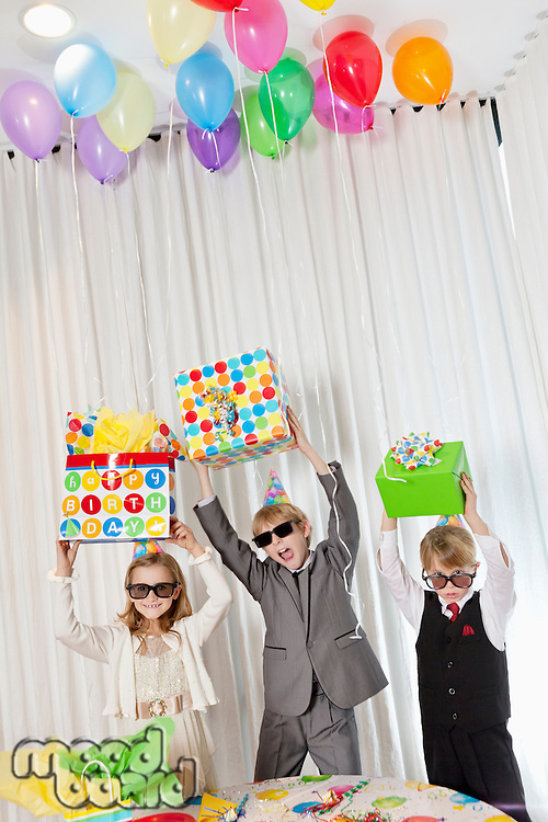 Brothers and sister wearing sunglasses holding gift aloft while shouting