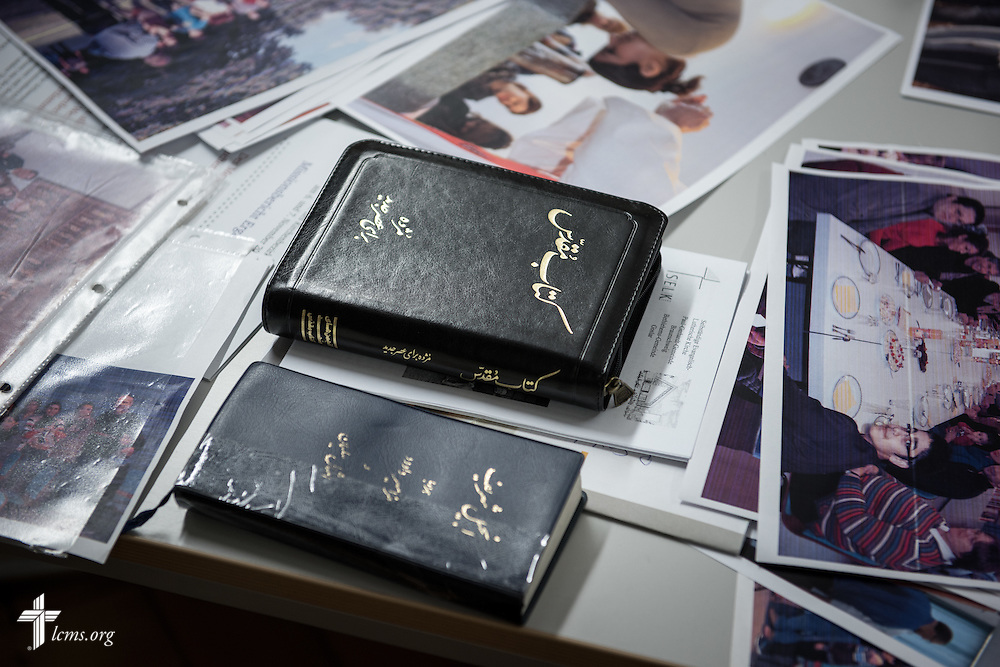 Translated Bibles lay on the table next to photographs of refugees helped by the Rev. Thomas Seifert, pastor of Paul-Gerhardt Gemeinde, a SELK Lutheran church in Braunschweig, Germany, during a planning meeting at the SELK headquarters on Thursday, Nov. 12, 2015, in Hannover, Germany. LCMS Communications/Erik M. Lunsford